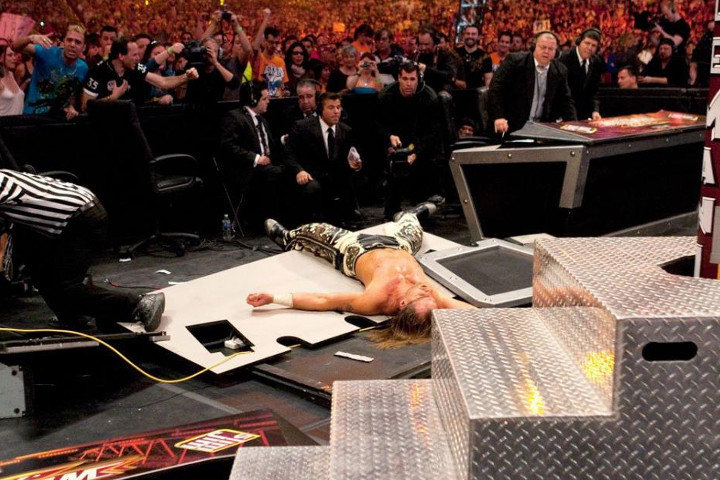 WWE Superstar Shawn Michaels laying on what remains of the Spanish announcer table